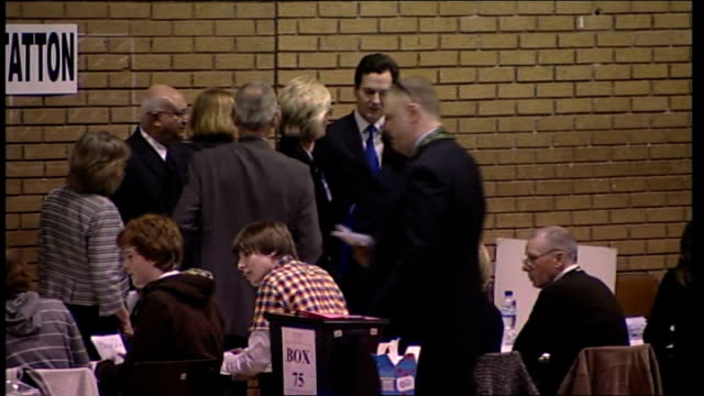 vote counting in large hall/ george osborne mp standing chatting with others next to 'tatton' sign on wall - george osborne stock videos & royalty-free footage