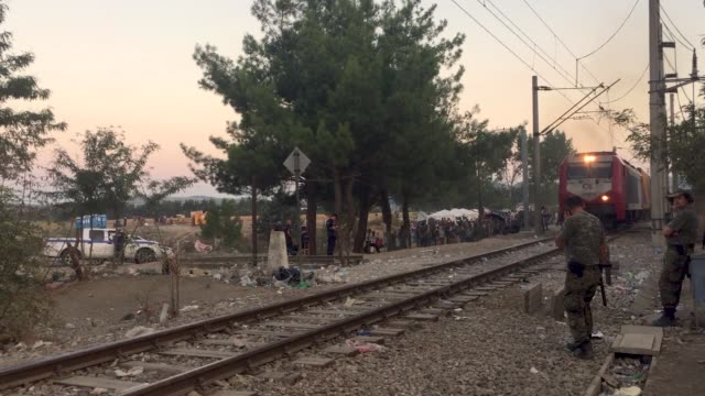 Macedonian border guard watches over a camp full of Syrian Iraqi and Pakistani migrants shortly after they crossed the Macedonian border from Greece...