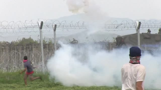 Macedonian police fire tear gas at migrants who were trying to pull down barbed wire from the border fence at the Idomeni in protest