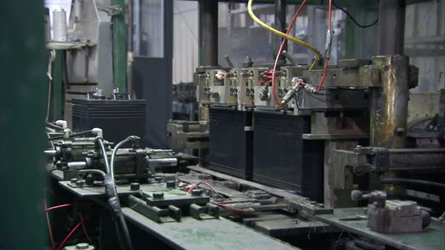 a machine adds components to wet-cell batteries on an assembly line. - battery stock videos & royalty-free footage