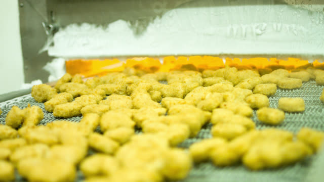 Machine baking nuggets at a chicken factory