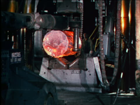 1946 machine carrying molten cylinder + placing it in machine in factory / industrial
