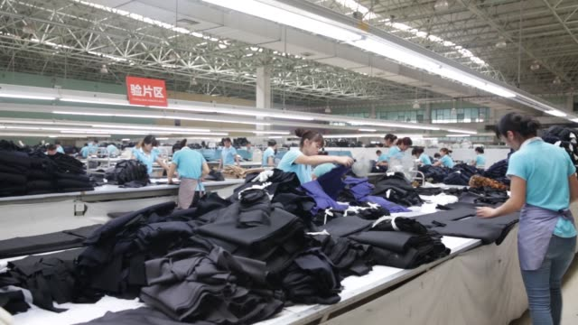 A machine cuts fabric at a factory operated by the Shandong Ruyi Technology Group in Jining China on Monday May 30 Employees arrange fabric An...