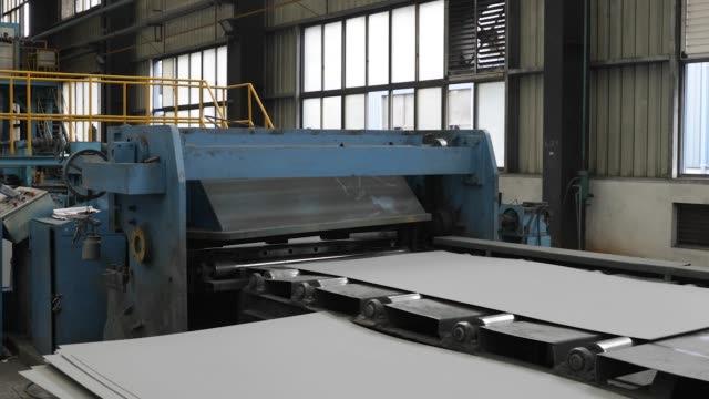 A machine cuts flattened metal sheets in the pressing shop at the SingamasContainer Holdings Ltd factory in Qidong China on Thursday June 22 2017 CU...
