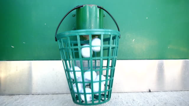 vídeos de stock e filmes b-roll de machine filling the basket with golf balls on driving range - balde