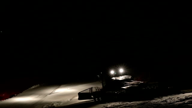 machine for leveling the ski slopes works at night. - snowplough stock videos & royalty-free footage