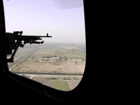 Machine gun aiming out window of US military helicopter flying over rural fields / Baghdad Iraq / AUDIO