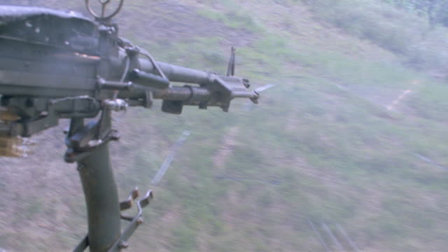 a machine gun fires out the side of a low flying helicopter. - vietnam war stock videos & royalty-free footage