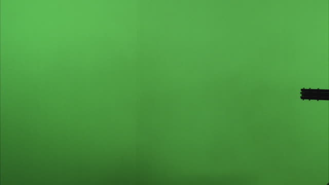 cu machine gun muzzle against green screen - sparare video stock e b–roll
