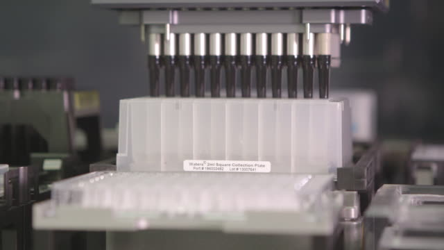 a machine in a laboratory automatically fills trays of sample pots with a solution. - medical sample stock videos & royalty-free footage