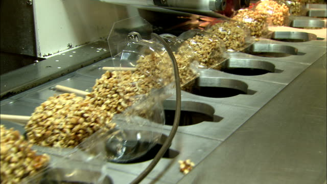 a machine packages caramel apples. - toffee stock videos & royalty-free footage