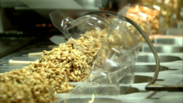 a machine places plastic lids on caramel apples as they move on a conveyor. - karamell stock-videos und b-roll-filmmaterial