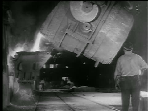 B/W 1942/43 machine pouring molten steel in factory / factory worker standing in foreground / newsreel