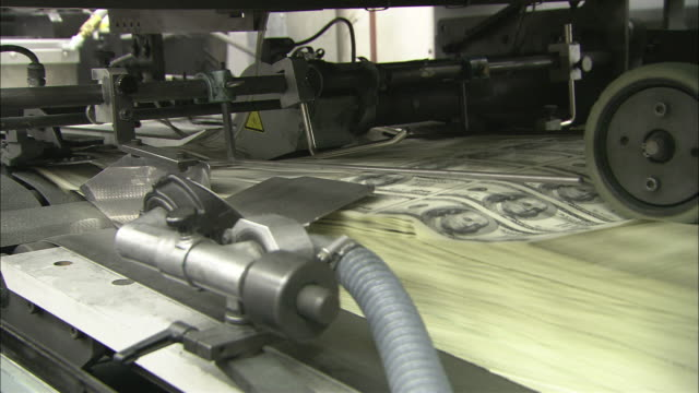 a machine prints sheets of us dollar bills. - printing out stock videos and b-roll footage