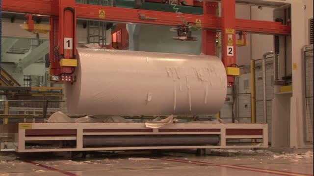 a machine processes a large roll of paper. - paper mill stock videos & royalty-free footage