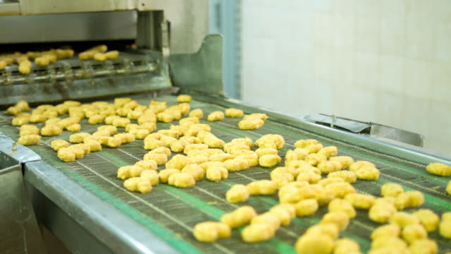 machine processing nuggets at a food factory - convenience food stock videos and b-roll footage