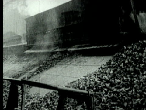 1927 b/w montage dissolve ws machine releasing coke at retort coke oven plant/ pennsylvania, usa - kohlengrube stock-videos und b-roll-filmmaterial