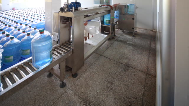 cu machine rotating full plastic water bottles - bottling plant stock videos and b-roll footage