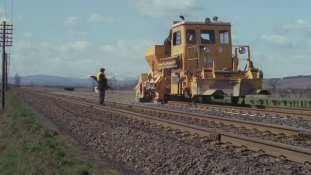 vídeos de stock e filmes b-roll de 1969 montage machine smoothing down the rock bedding along the british railways / united kingdom - british rail