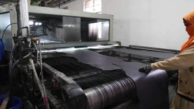 machine uses spray guns to treat a sheet of leather at the jalandhar leather pvt. tannery in jalandhar, punjab, india, on saturday, jan. 21, 2017 - weaponry stock videos & royalty-free footage