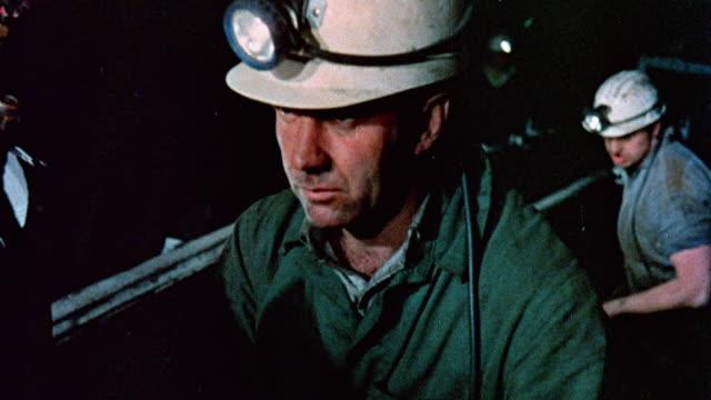 vídeos de stock, filmes e b-roll de 1976 montage machinery and workers facilitating the mining and transportation of coal / doncaster, england, united kingdom - mina de carvão