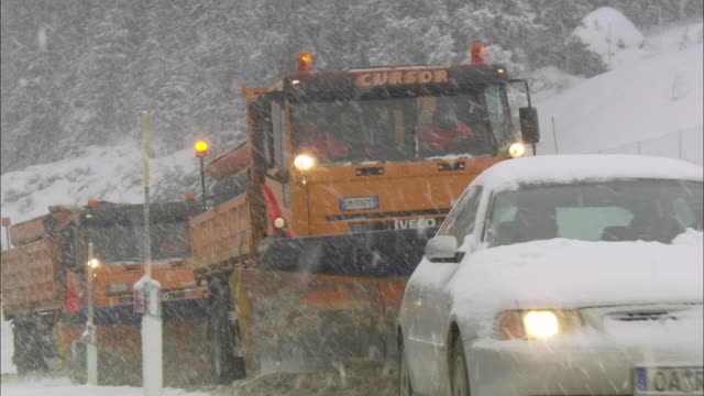 Machinery with snowplough cleaning road