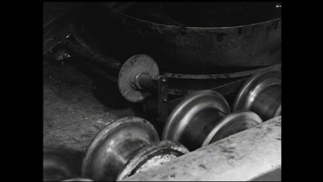 machinery wrapping cloth around coil of wires and worker rolling it away; large wire coils being unspooled upward; copper bar passing by on the... - 1940 1949 video stock e b–roll