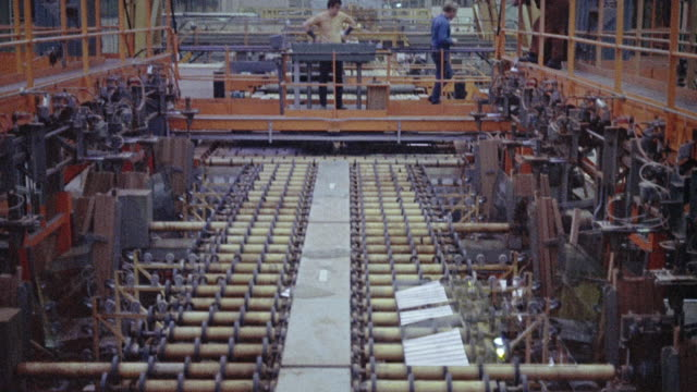1973 montage machines moving glass sheets on a conveyor and molten glass shaping television screens in a factory / united kingdom - 1973 stock videos & royalty-free footage