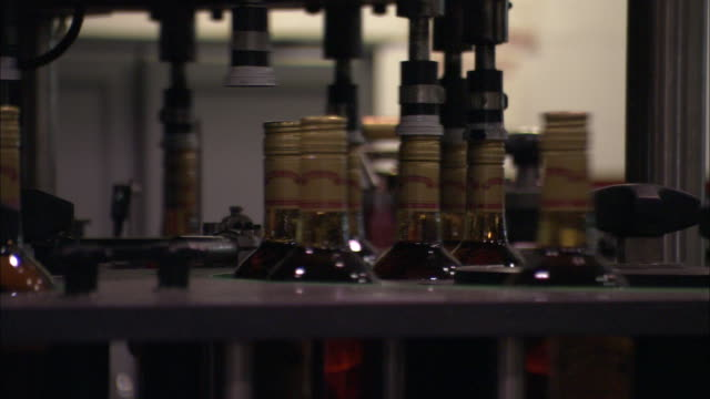 Machines seal bottles of rum that move along a conveyor belt.