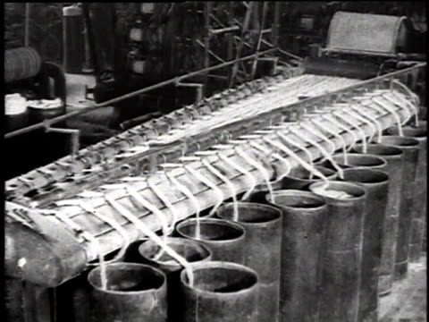 1921 montage machines spinning out asbestos yarn onto big spindles and workers unloading it from the machine / waukegan, illinois, united states - アスベスト点の映像素材/bロール