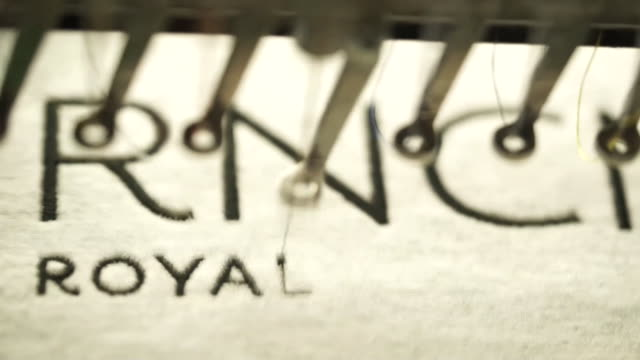 vídeos de stock, filmes e b-roll de machines stitching words at a clothing factory in manchester - ponto de costura