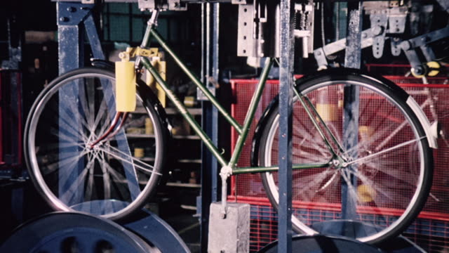 1974 montage machines testing various bicycle parts and bicycles moving on an assembly line in a factory / united kingdom - 1974 bildbanksvideor och videomaterial från bakom kulisserna