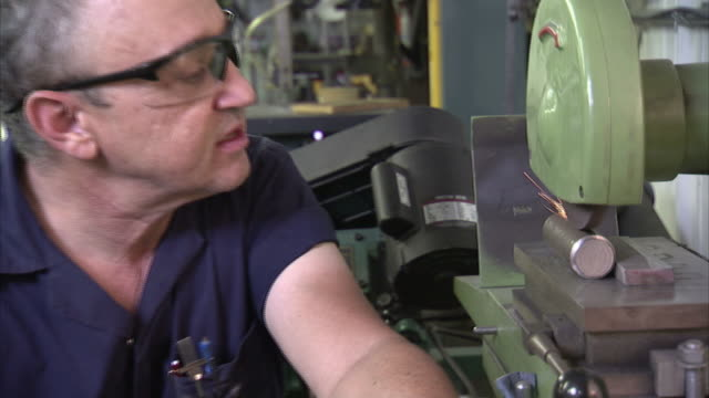 A machinist operates an aluminum filing and sealing machine.