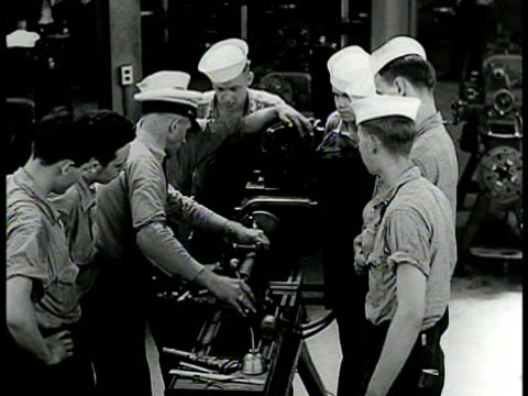 stockvideo's en b-roll-footage met machinists' mate training cu machinists' mate rating badge int vs instructor showing machinists in training lathe ms cadet using caliper tool to... - 1942