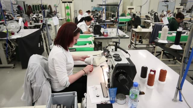 vidéos et rushes de machinists sit at sewing machines in workshop of bentley motors upholstery department working on pieces of fabric for car interior bentley motors... - atelier d'artisan