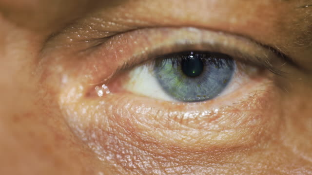 stockvideo's en b-roll-footage met macro close view of older man's blue color left eye - netvlies