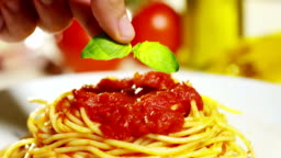 macro detail of Italian pasta with tomatoes and parmesan cheese and basil.