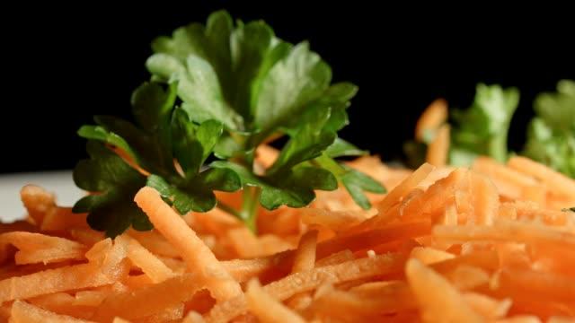 vidéos et rushes de macro dolly: carottes râpées avec du persil - touche de couleur