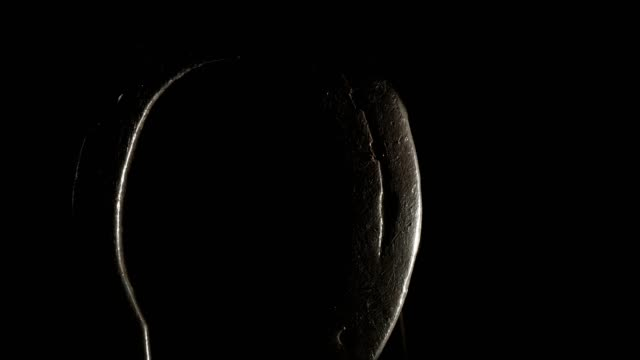 macro dolly: horseshoe on black background - horseshoe stock videos and b-roll footage