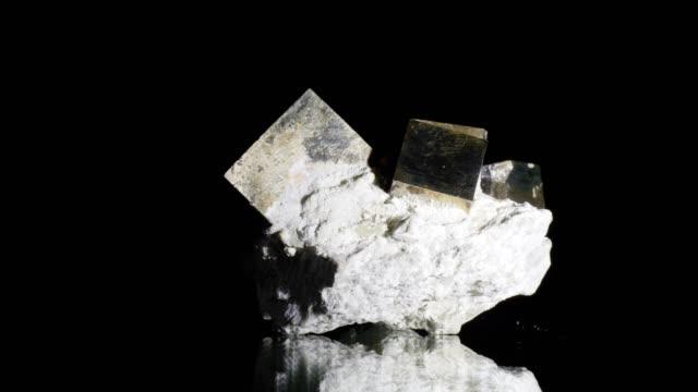 vidéos et rushes de dolly de la macro: pyrite sur fond noir - pierre précieuse