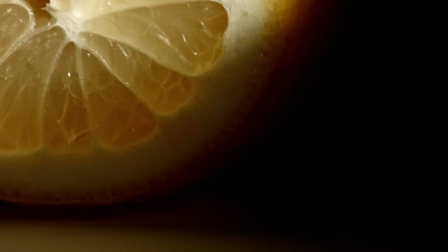 Macro dolly: Sliced lemon on black background