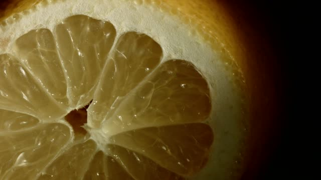 vídeos de stock e filmes b-roll de macro dolly: sliced lemon on black background - ágata