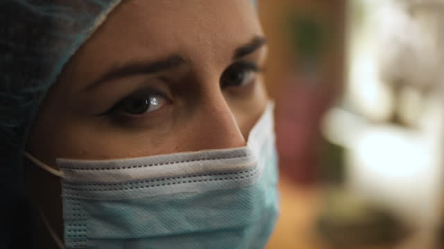 vídeos de stock e filmes b-roll de macro eyes: female doctor nurse in medical mask looks at patient with almost crying eyes - bata cirúrgica