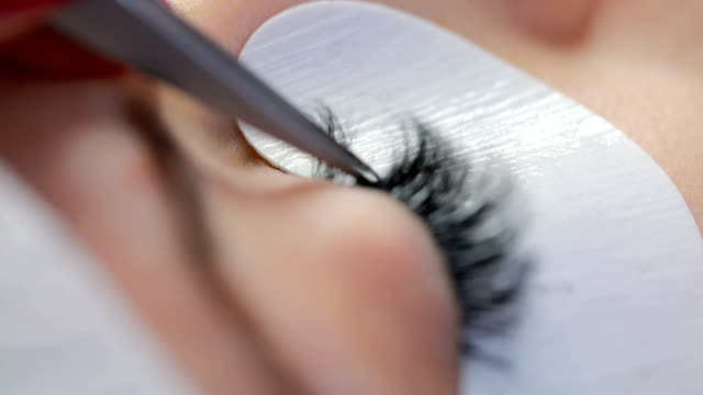 macro of extension eyelash application - beauty spa stock videos & royalty-free footage