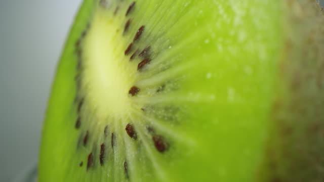 vídeos de stock e filmes b-roll de macro of rotating kiwi cut in half - frescura