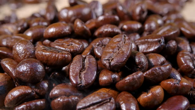macro shot dark coffee bean with smoke - roasted coffee bean stock videos & royalty-free footage
