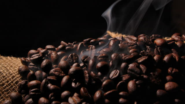 vídeos y material grabado en eventos de stock de macro shot dark coffee bean with smoke - construir