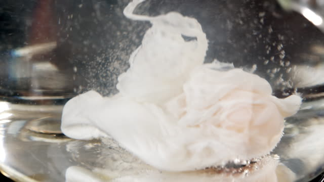 macro shot of an egg being dropped into boiling water. - swirl stock videos & royalty-free footage