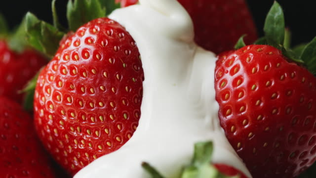 macro shot of cream being poured over glass bowl of strawberries against black background. - juicy stock videos & royalty-free footage