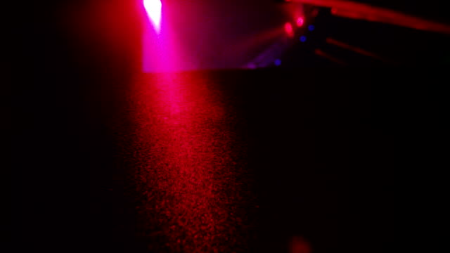A macro shot of Holi dust floating through the air as a DJ mixes to color Holi party in slow motion